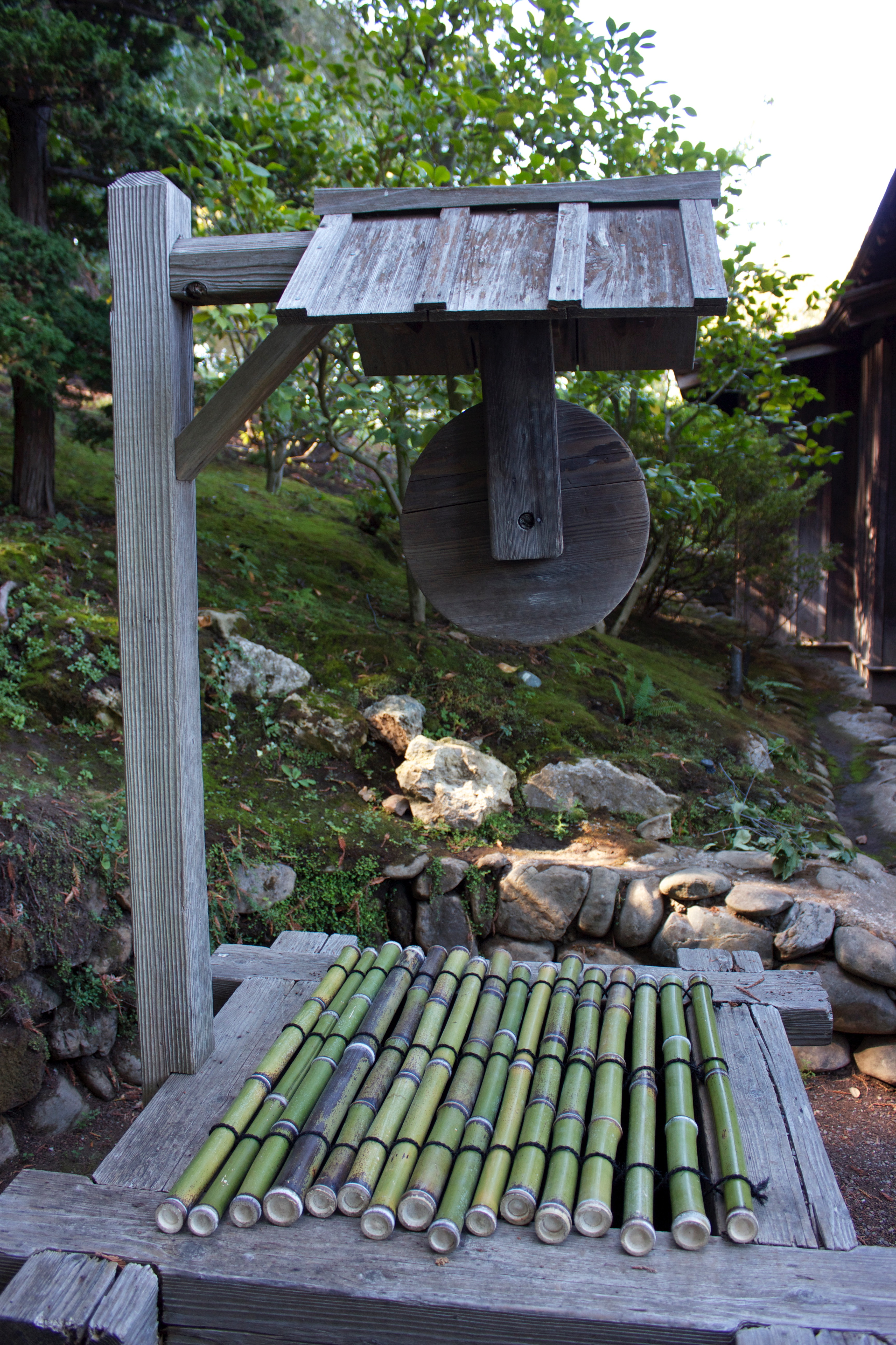 An old wooden water well in a Japanese garden, covered by bamboo stalks strung together.