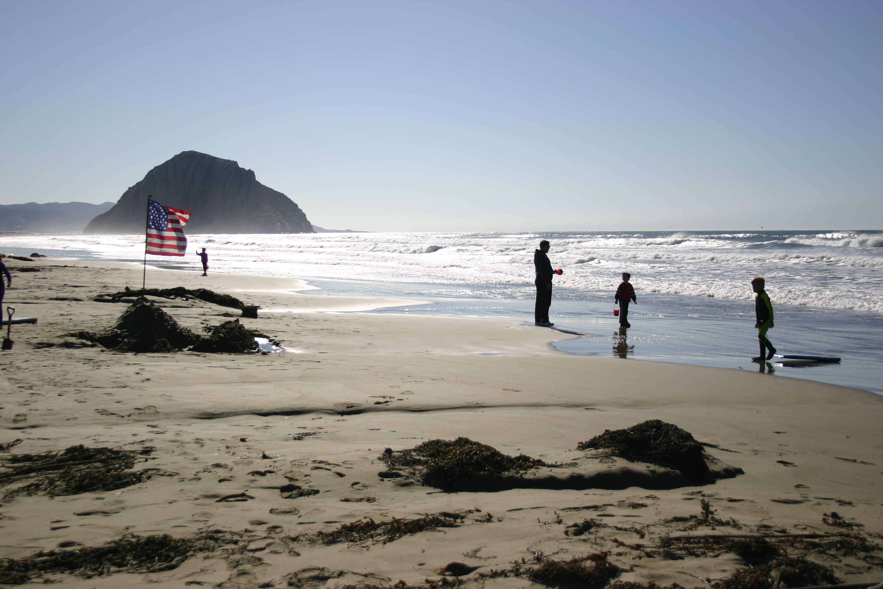 An American flag flies on the beach near Morro Rock while children and adults play in the water nearby.