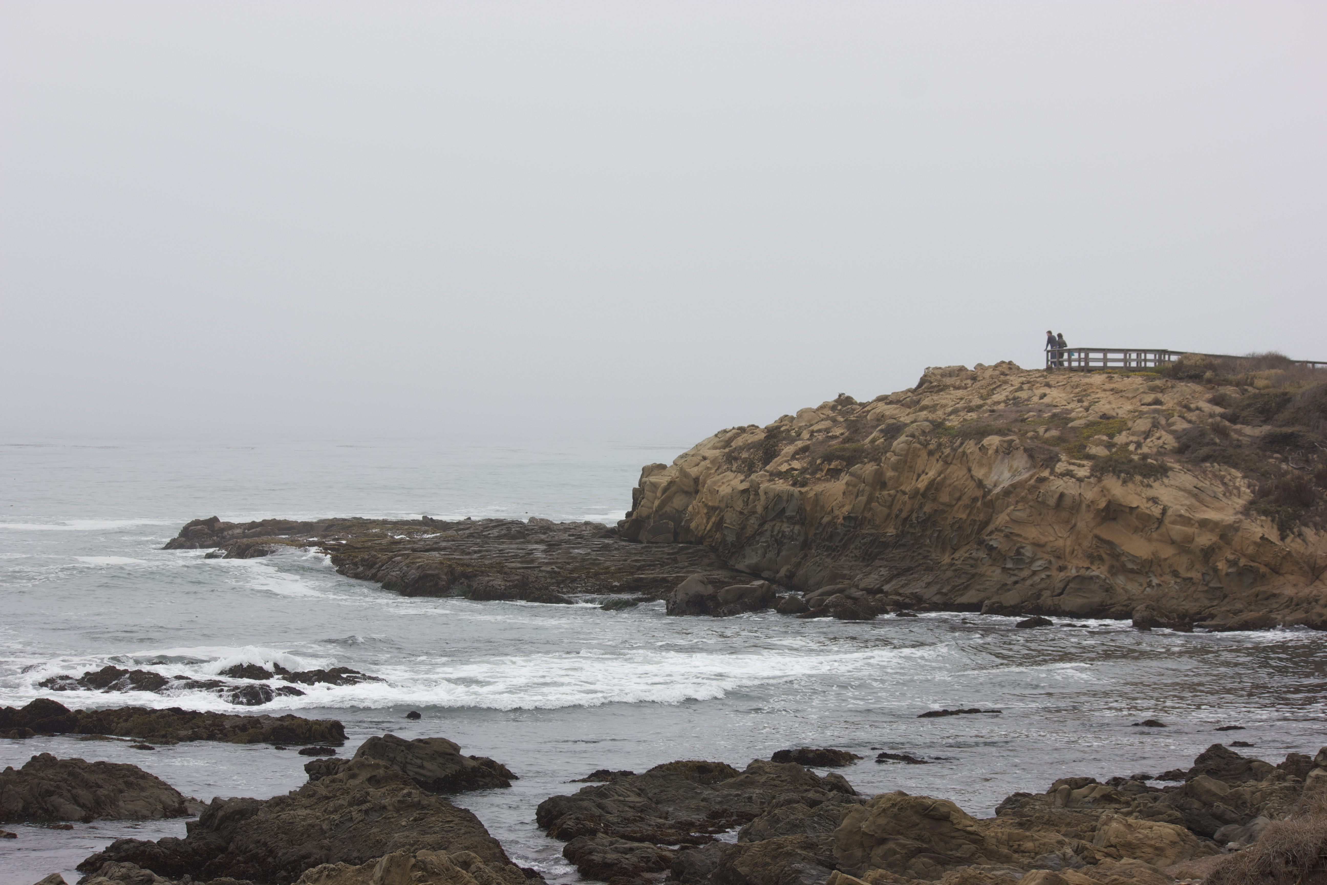 Two people standing in the distance on a rocky coastal outcropping, looking at the ocean.