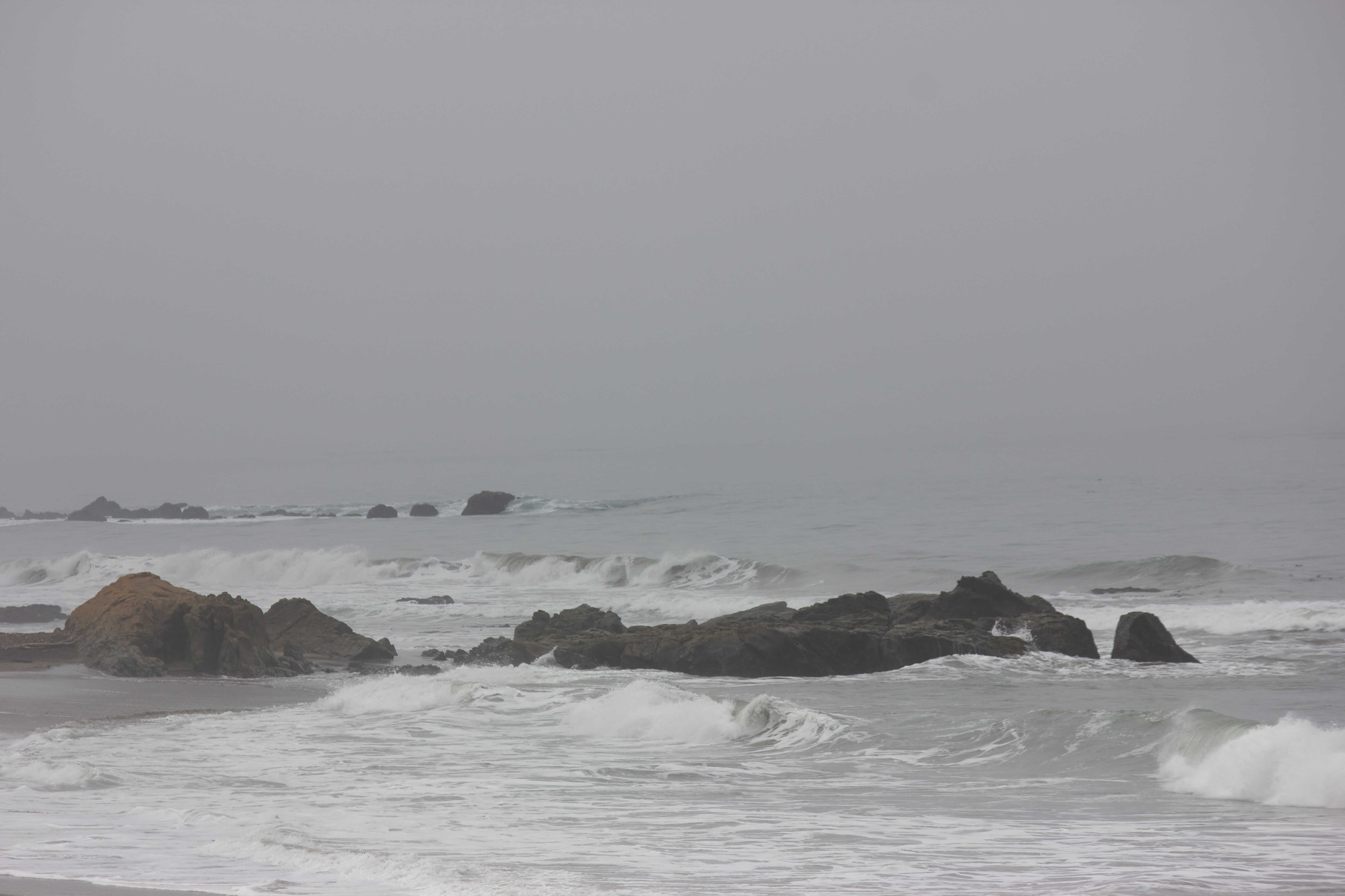 Waves near the rocky coast before a foggy blurred horizon.