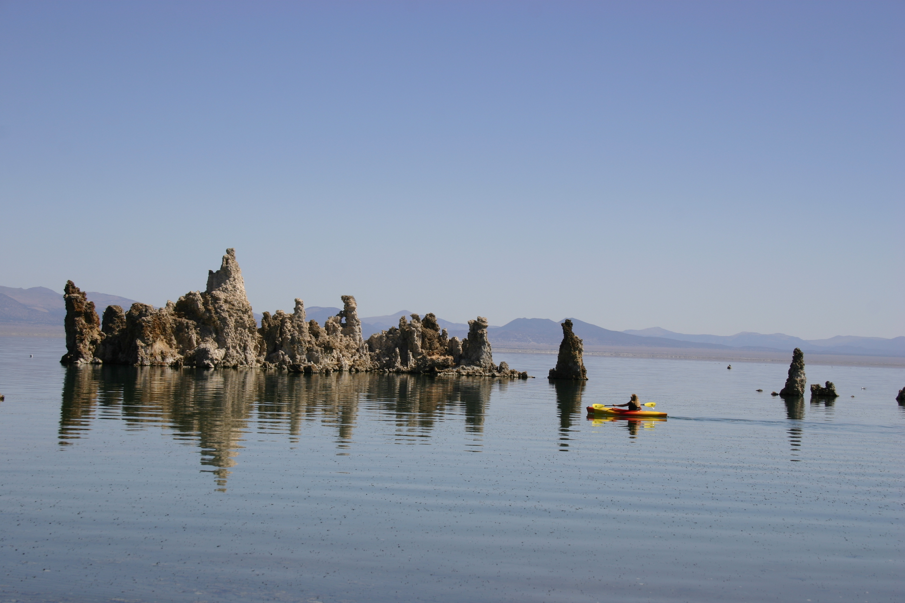 A brightly colored kayaker paddles by tufa towers in Mono Lake.