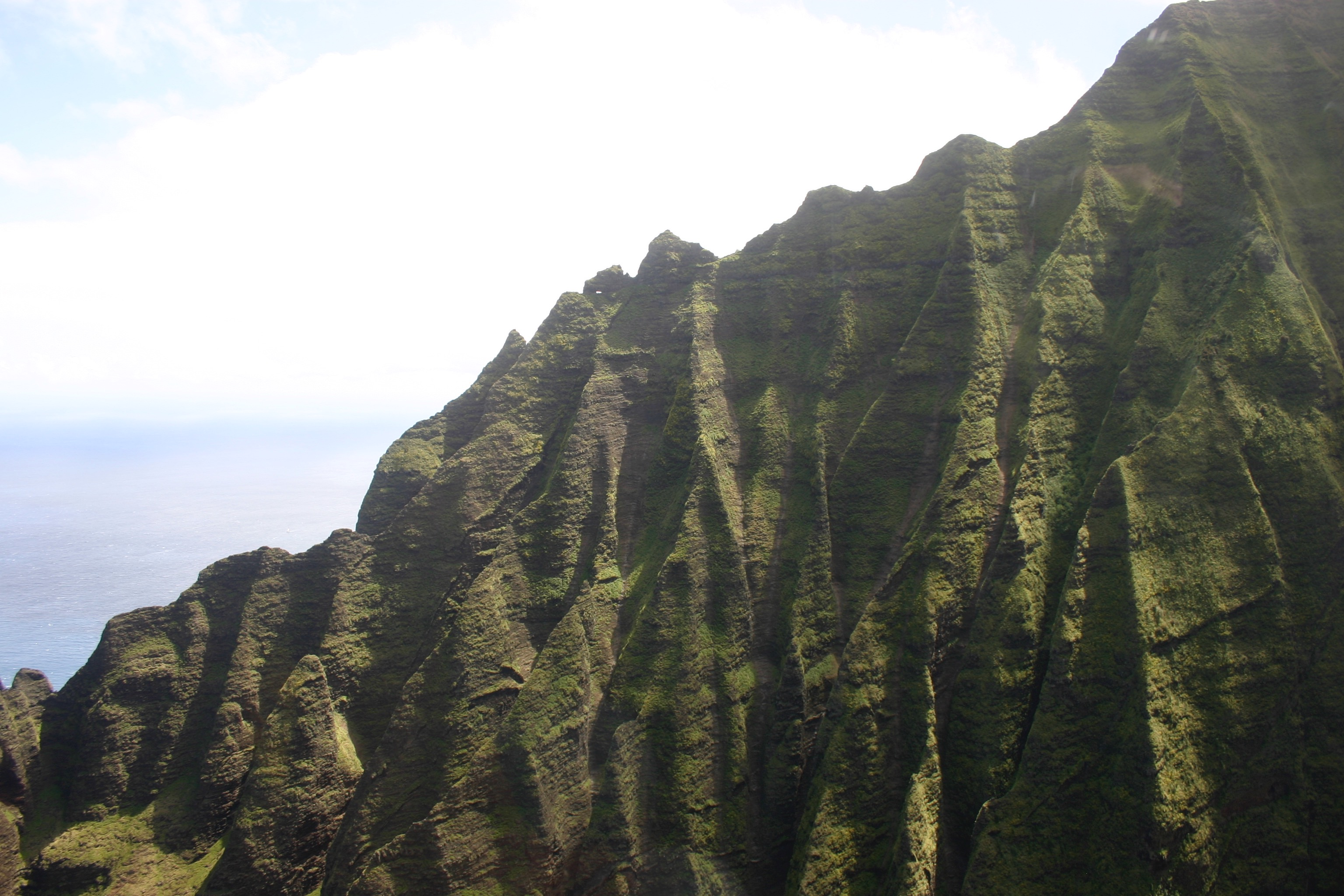 The rugged green cliffs of the Nā Pali coast, seen from a helicopter.