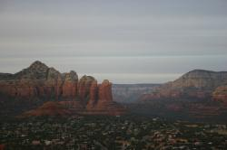 Red rock mountains tower over the city of Sedona at twilight.