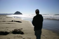 A man stands on the beach, gazing toward Morro Rock.