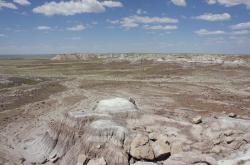 Painted Desert landscape with a cloud-dotted blue sky.