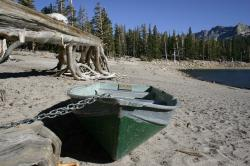 A green rowboat chained on the shore at Horseshoe Lake.