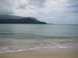 Gentle waves lap the shore at Hanalei Bay.