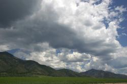 A sky full of clouds threatens to rain on hills and a green plain.