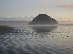 Morro Rock reflected in rippled wet sand and backed by fluffy white clouds on a dreamy evening.