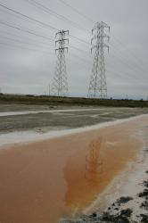High voltage tower reflected in the water of a pink salt marsh.