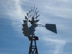 Water-pumping windmill against a cloudy blue sky.