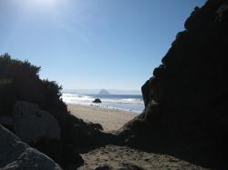 Rock formation on a beach landscape. Morro Rock centered in the distance.